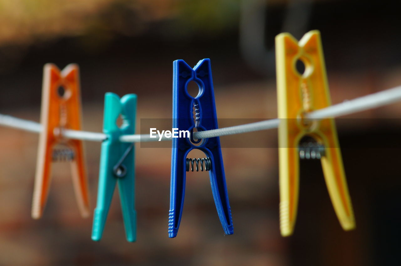 Close-Up Of Colorful Pins Hanging On Clothesline
