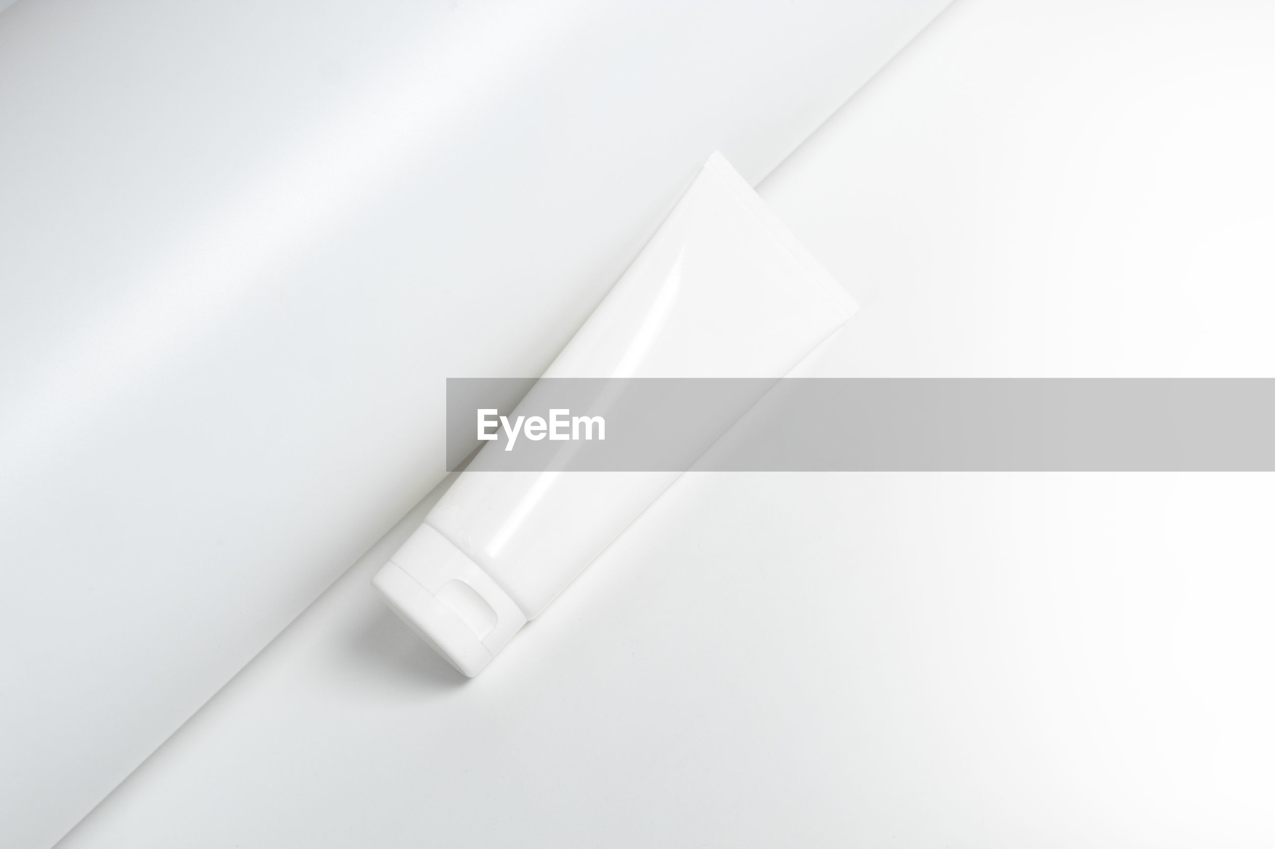 Close-up of cosmetic tube against white background