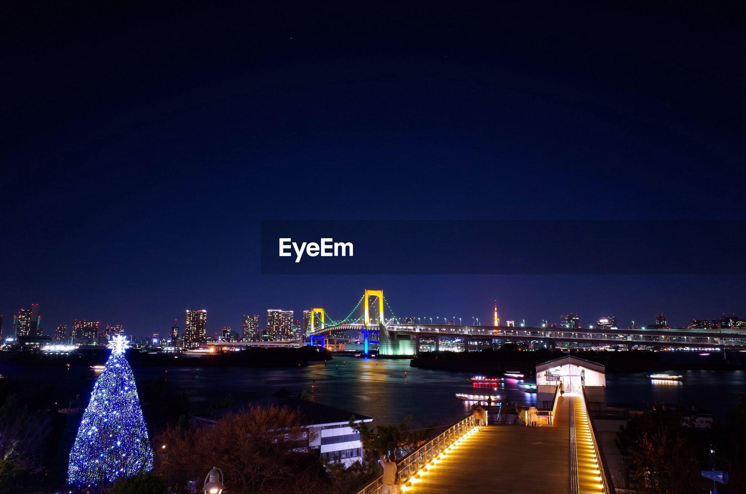 illuminated, night, water, built structure, architecture, city, river, reflection, connection, building exterior, copy space, clear sky, bridge - man made structure, lighting equipment, street light, waterfront, sky, cityscape, light, light - natural phenomenon