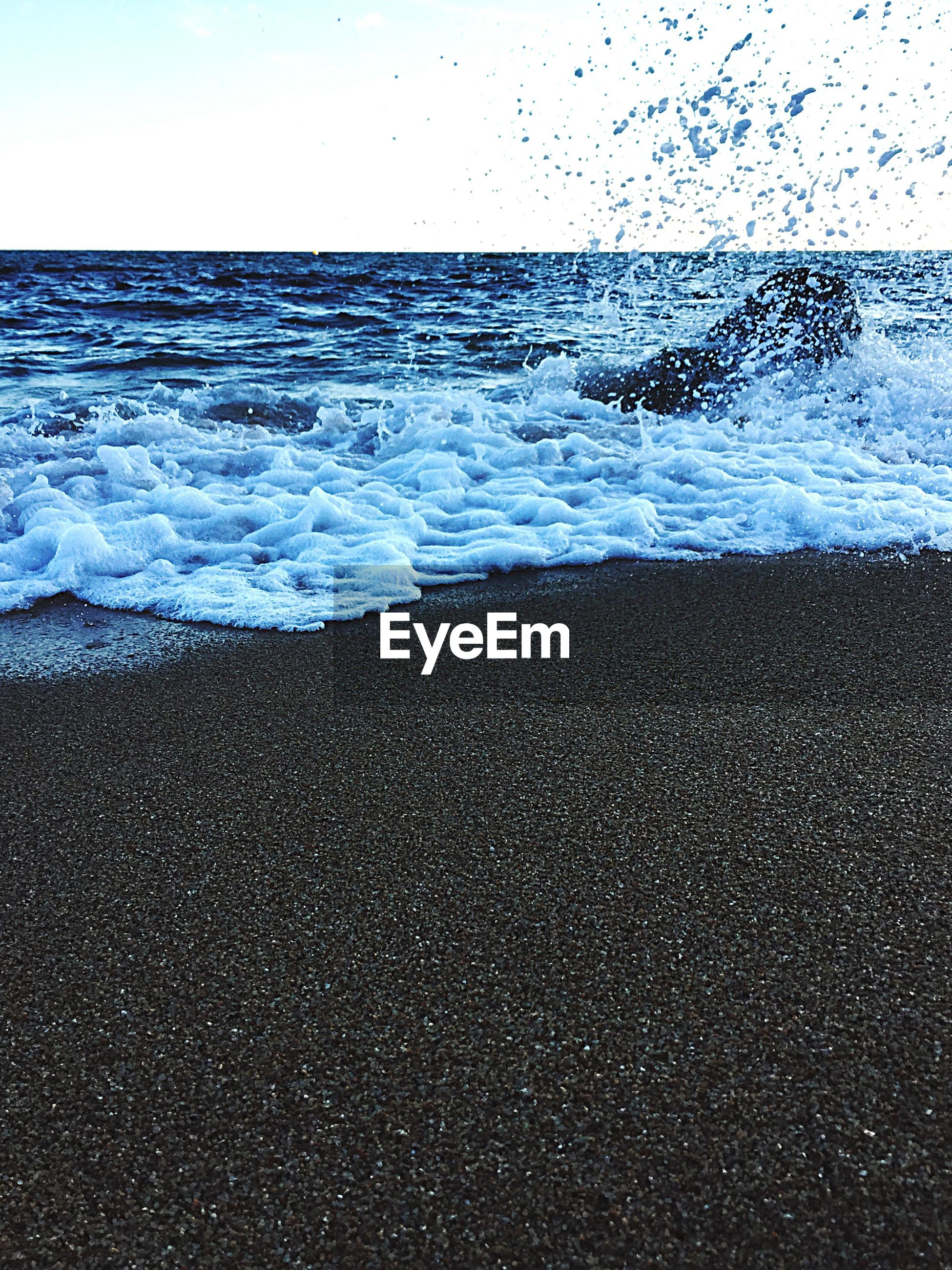 Waves splashing on rock at beach against sky