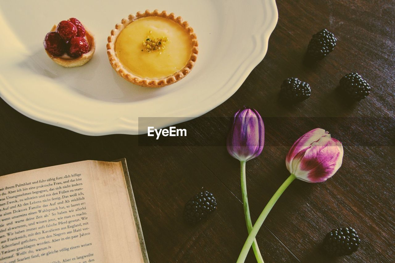 High Angle View Of Lemon Tart With Purple Tulips And Book On Table
