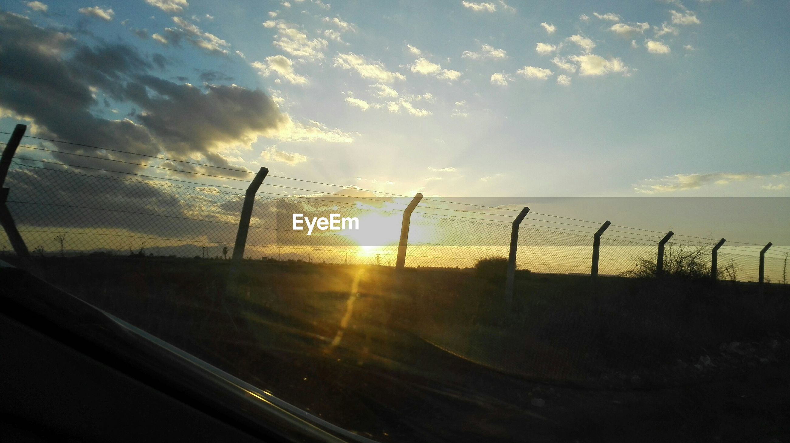 sunset, sun, silhouette, sky, sunlight, scenics, sunbeam, tranquility, lens flare, tranquil scene, orange color, nature, beauty in nature, cloud - sky, fence, idyllic, landscape, back lit, outdoors, no people