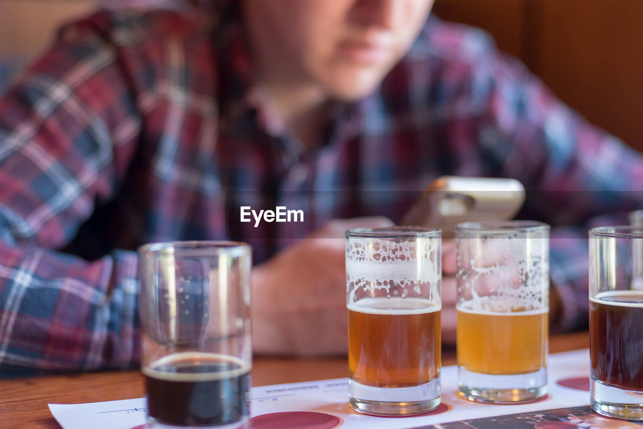 Midsection of man using phone while having beer at table