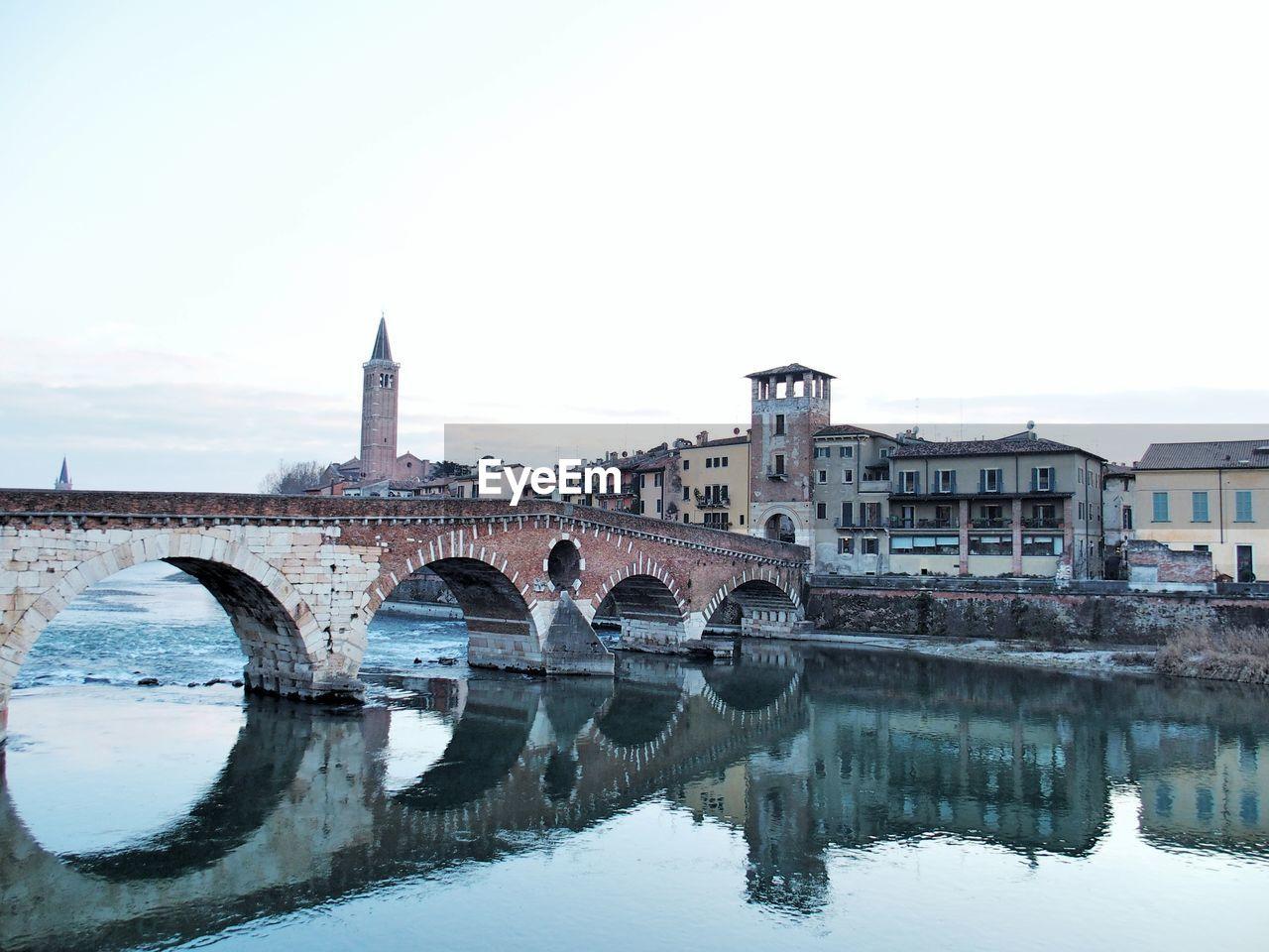 Ponte pietra reflecting in adige river against sky