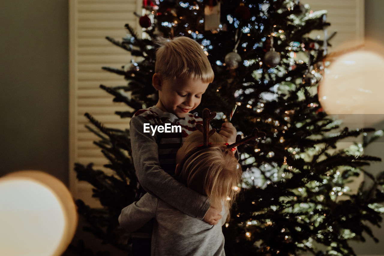 Siblings Standing Against Christmas Tree At Home
