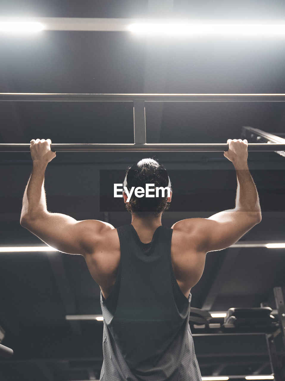 rear view, one person, sport, lifestyles, indoors, exercising, strength, healthy lifestyle, real people, standing, muscular build, three quarter length, determination, sports clothing, gym, men, adult, human arm, young adult, arms raised, human limb