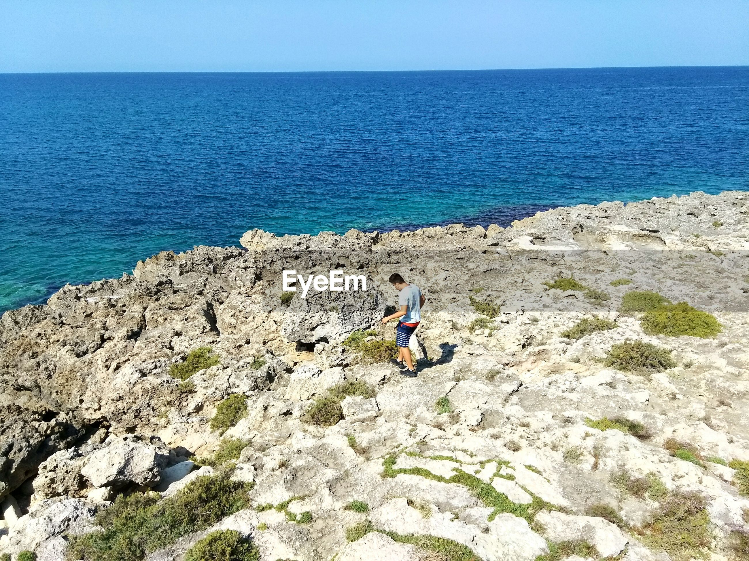 High angle view of man walking on rocks by ocean