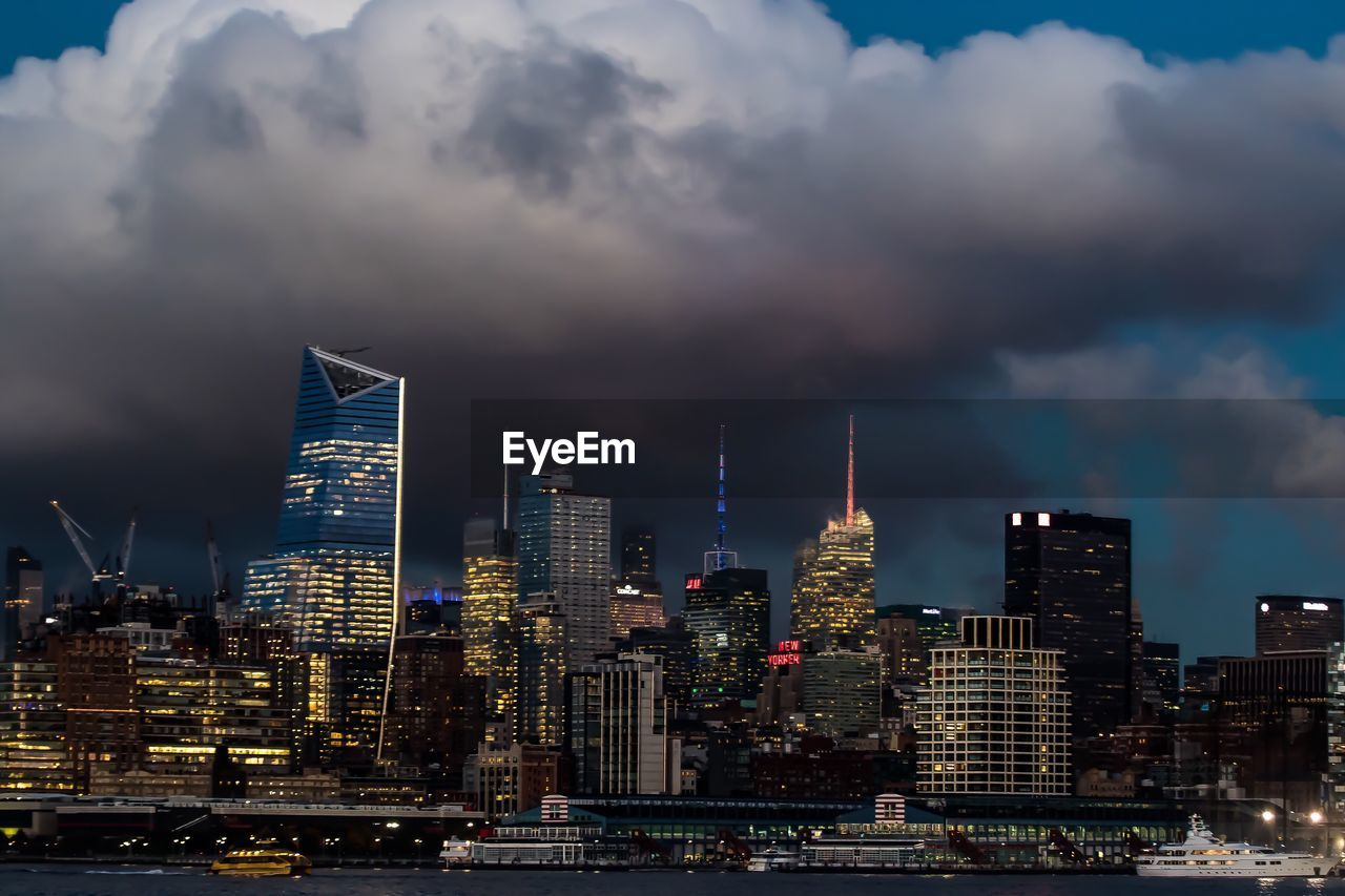 Illuminated Skyscrapers In City Against Cloudy Sky