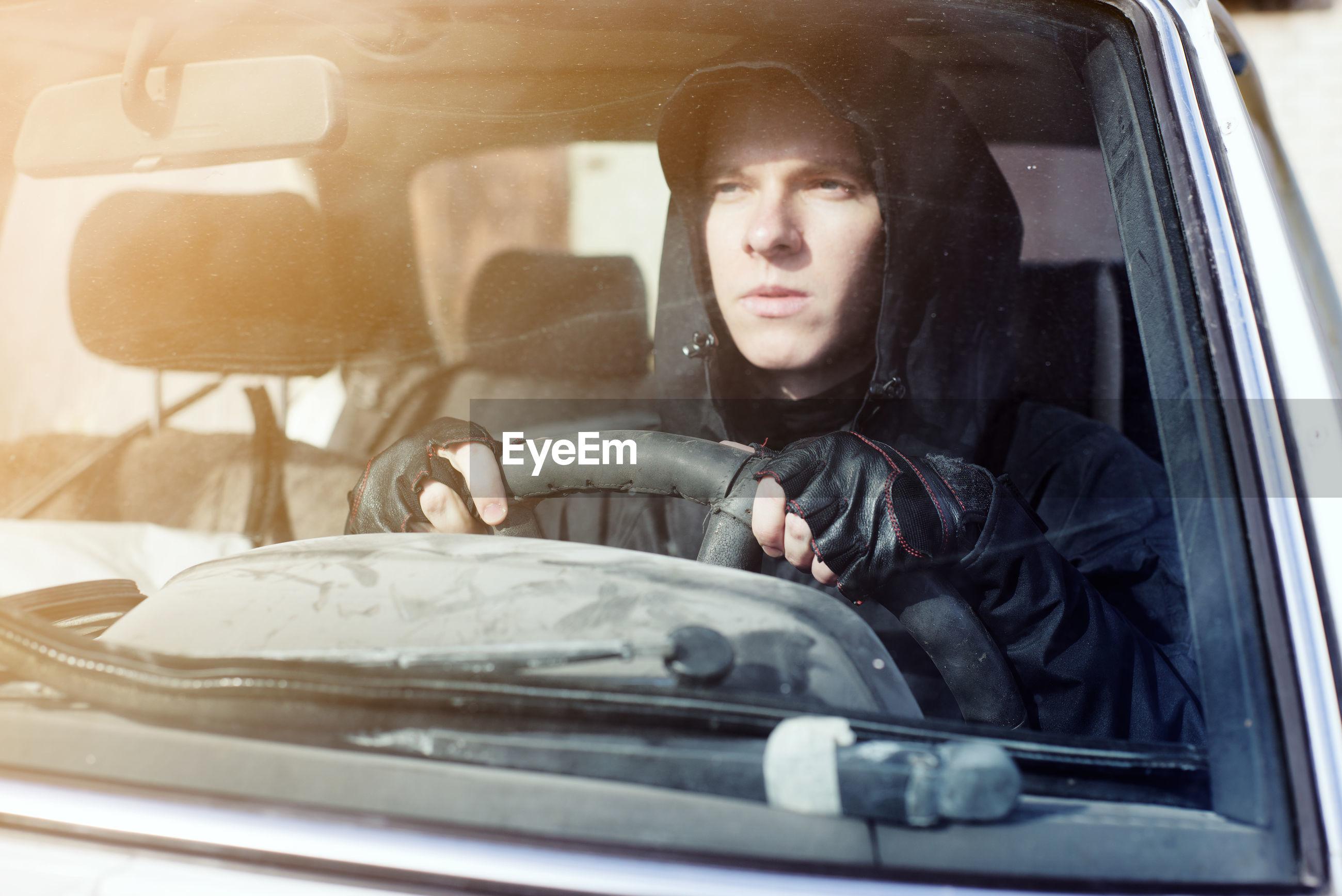 Man wearing hood driving car seen through windshield