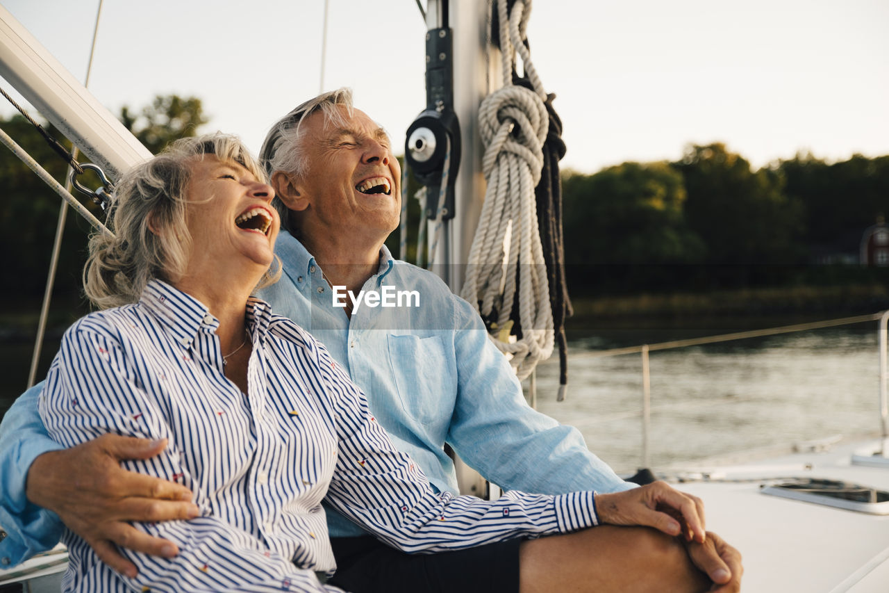 REAR VIEW OF COUPLE SITTING IN BOAT
