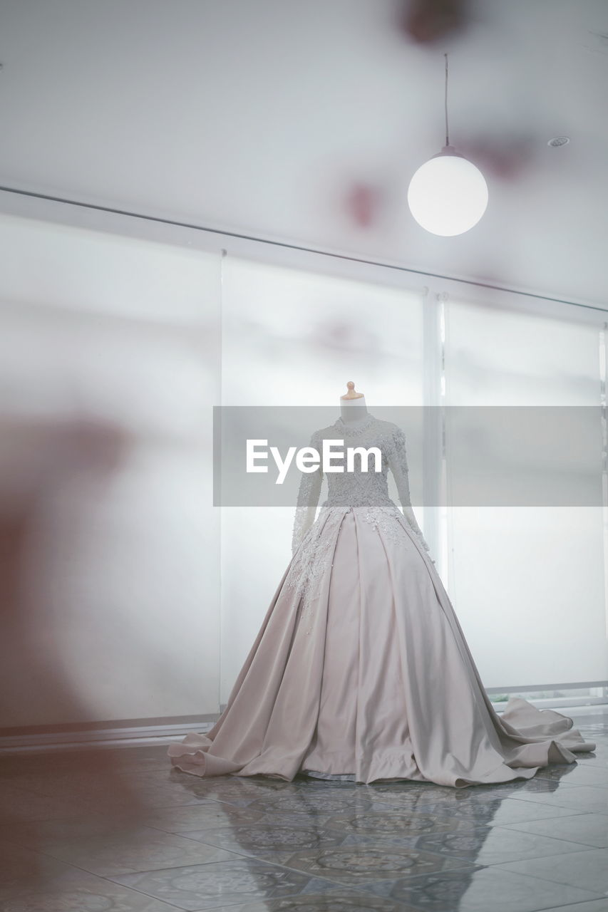 indoors, lighting equipment, no people, white color, illuminated, mannequin, wall - building feature, fashion, wedding dress, female likeness, day, celebration, reflection, human representation, dress, representation, focus on foreground, architecture, water, window, ceiling, electric lamp