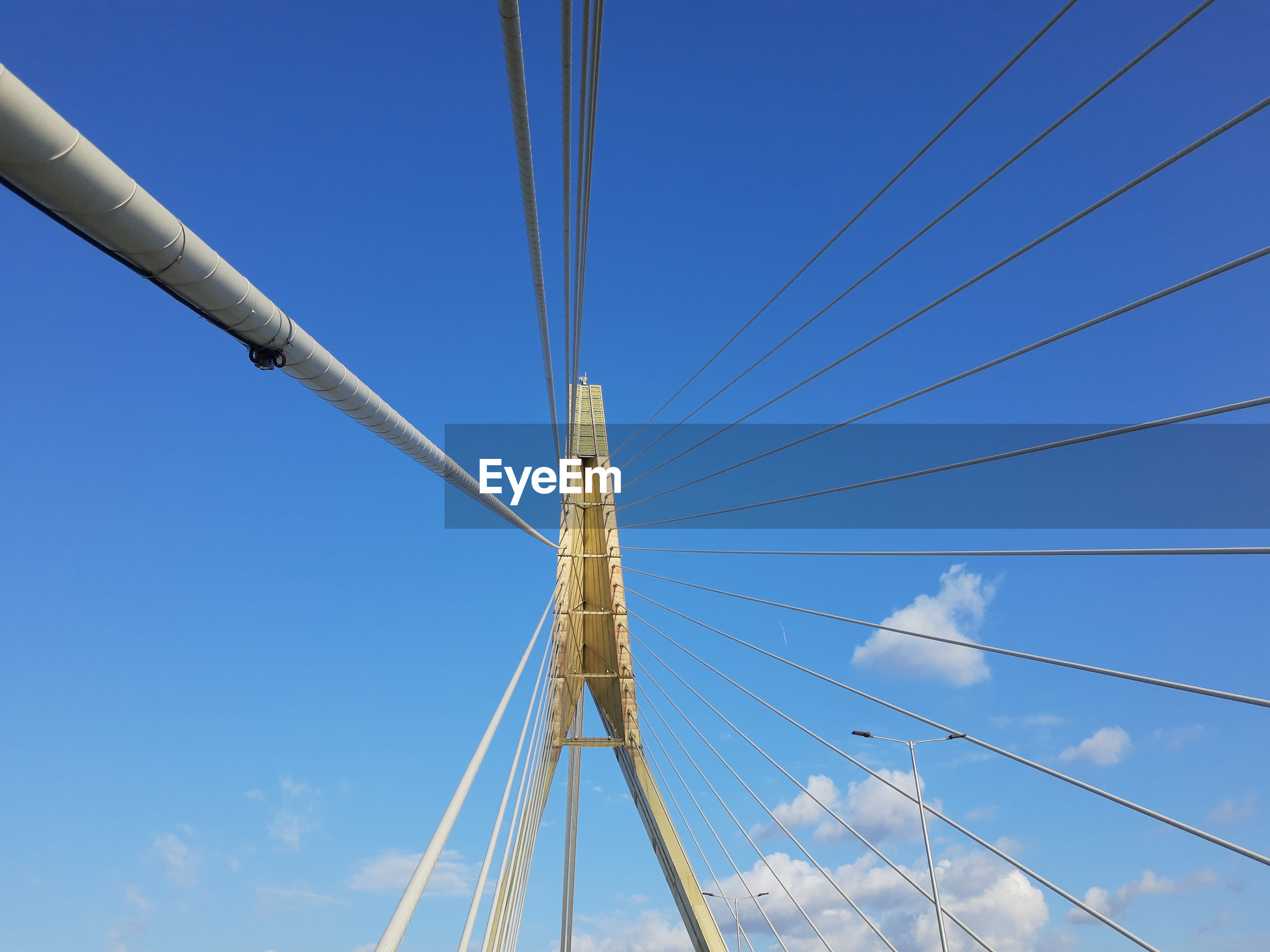 LOW ANGLE VIEW OF SUSPENSION BRIDGE CABLES AGAINST BLUE SKY