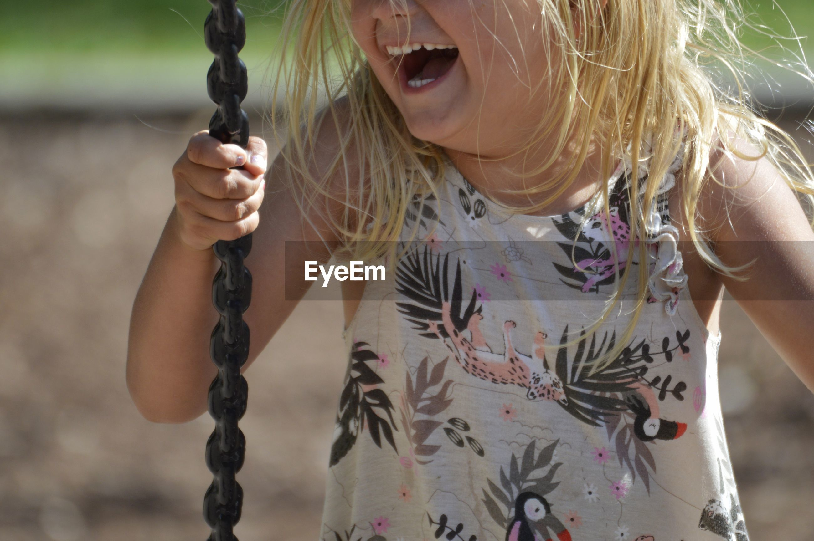 Midsection of cheerful girl on swing