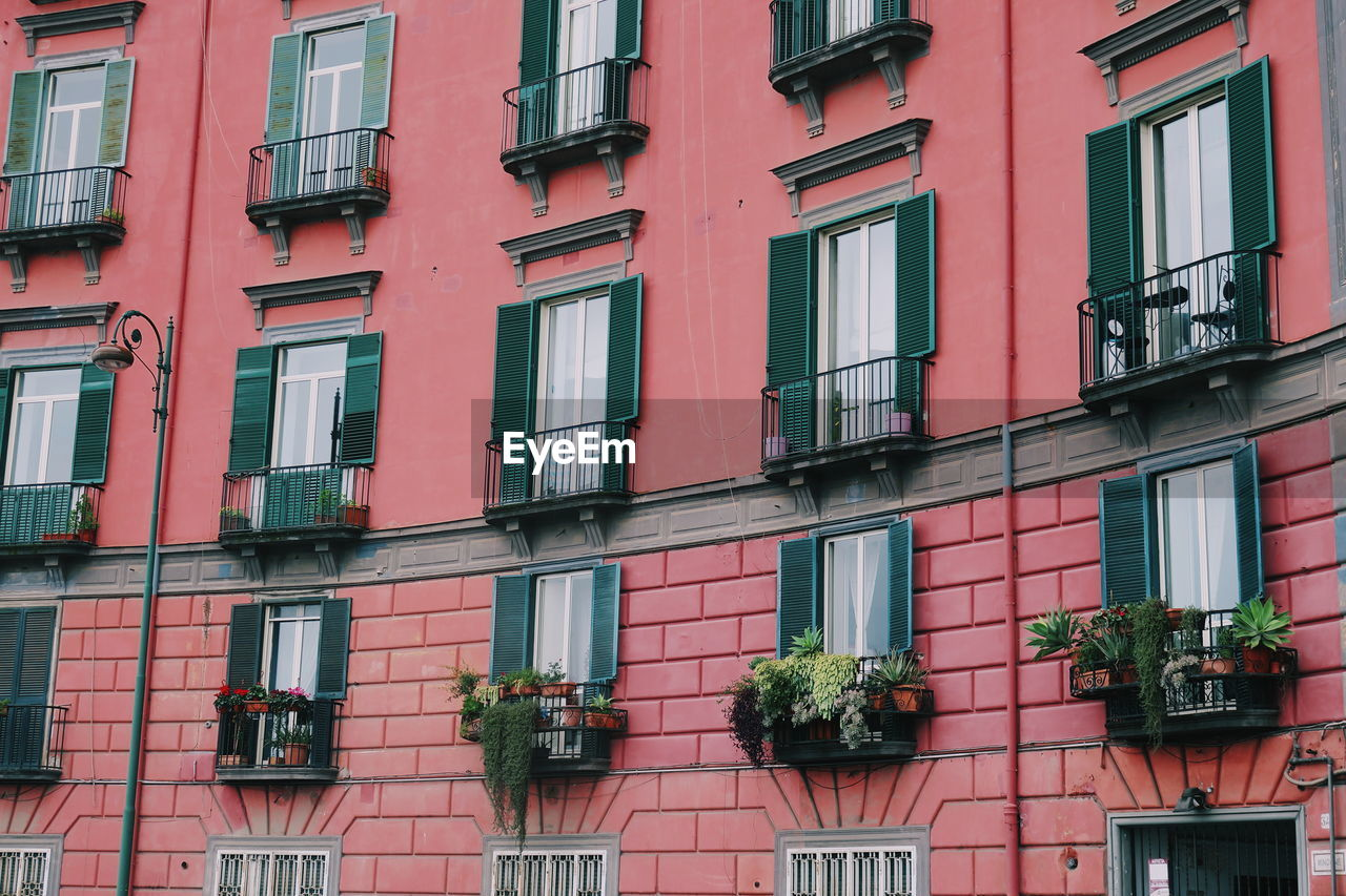 architecture, building exterior, built structure, window, building, residential district, low angle view, city, day, no people, outdoors, pink color, full frame, apartment, side by side, backgrounds, city life, in a row, glass - material, repetition