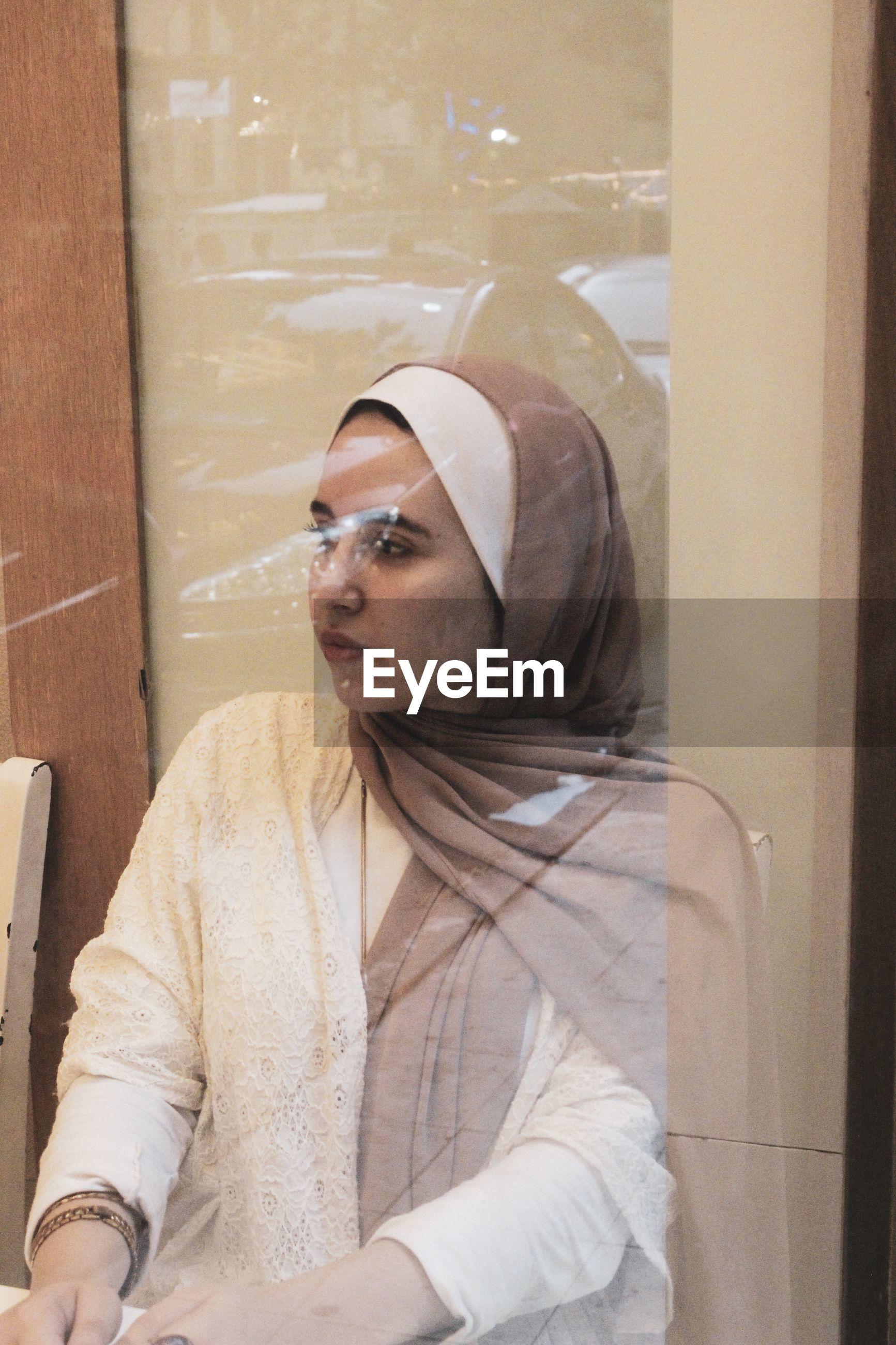Woman in headscarf seen through glass window