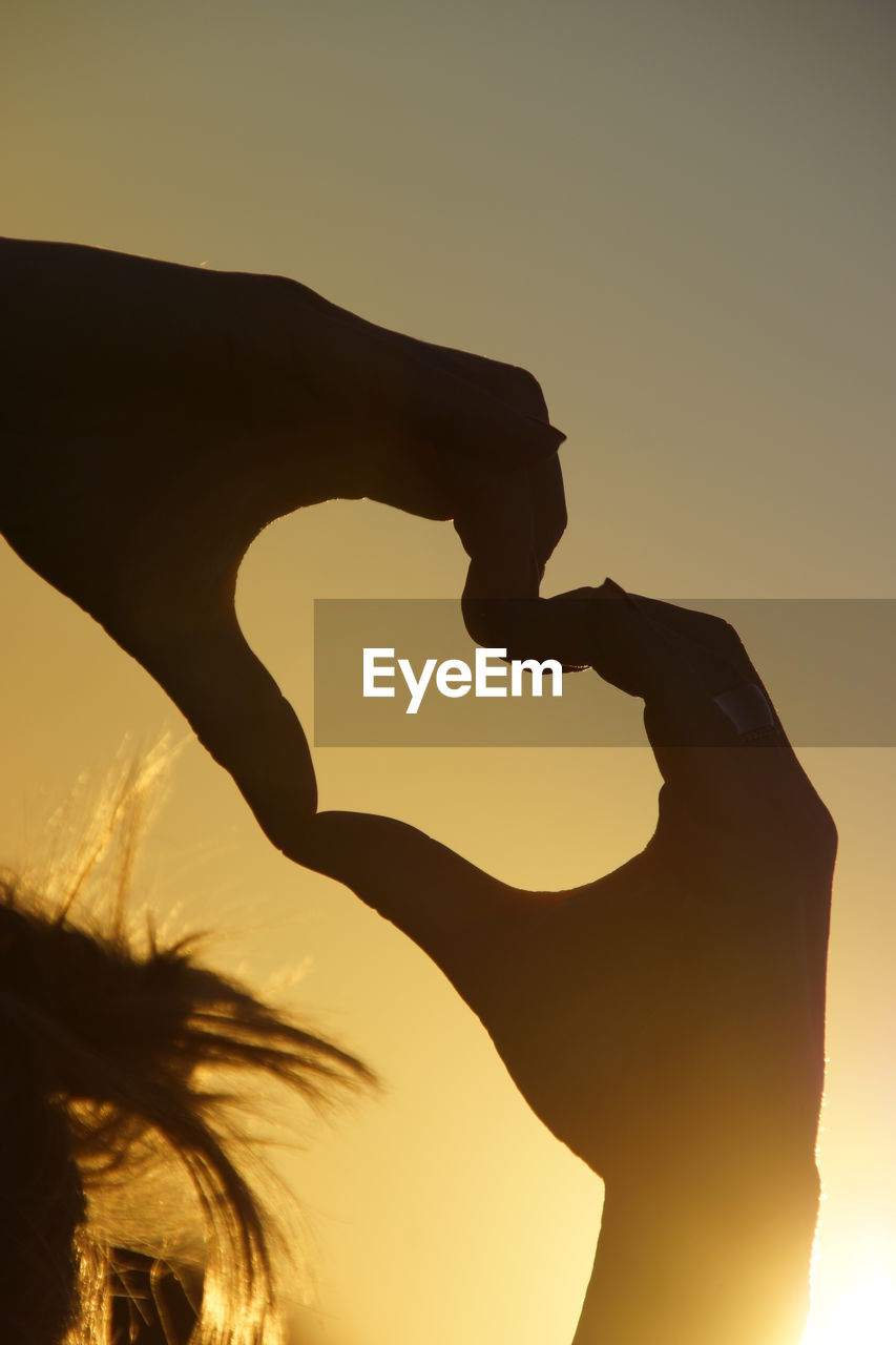 Silhouette woman making heart shape against clear sky at sunset