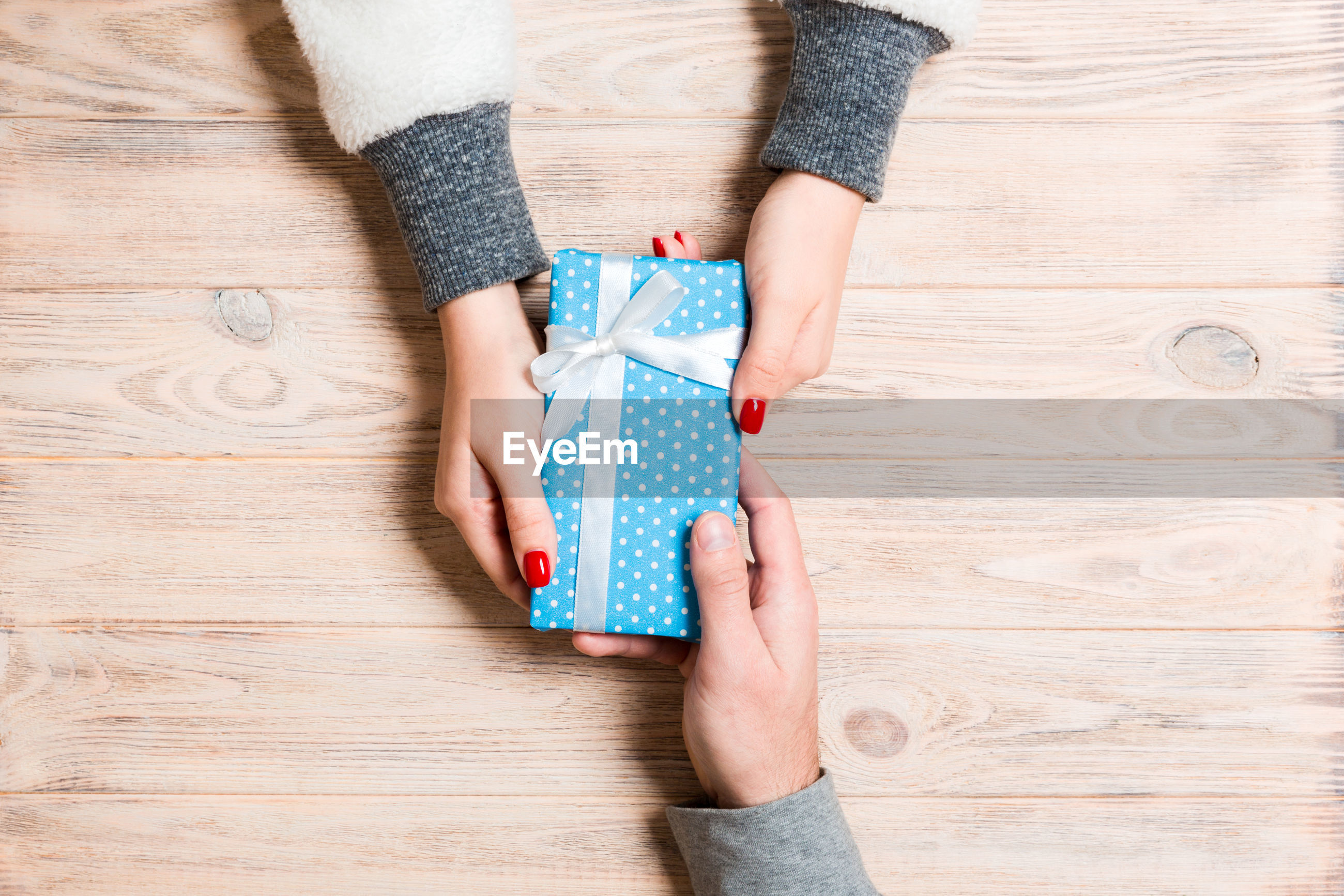 Directly above shot of man and woman holding christmas present on table