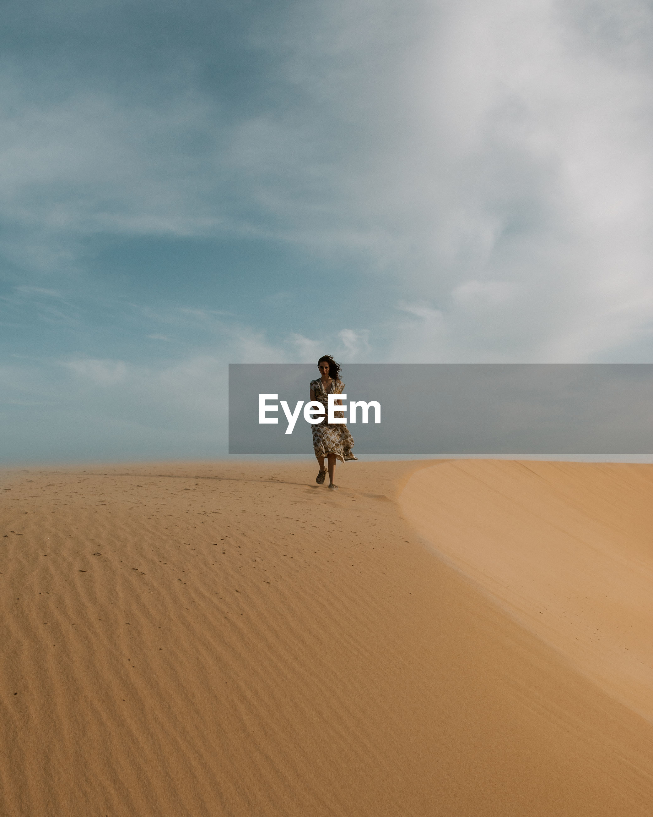 Woman standing on a sand dune in desert against sky