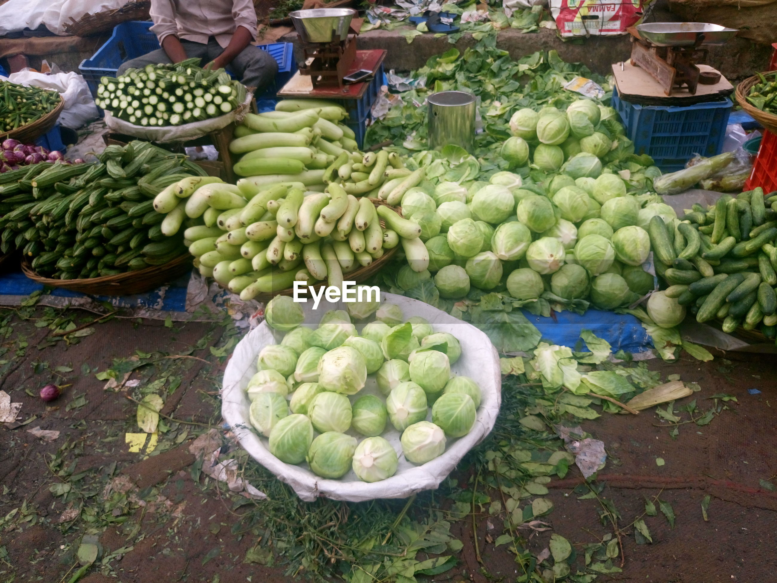 Vendor with various vegetables for sale at market