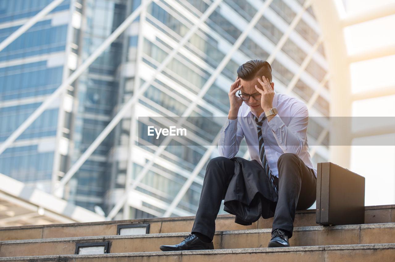 Businessman With Headache Sitting Against Buildings