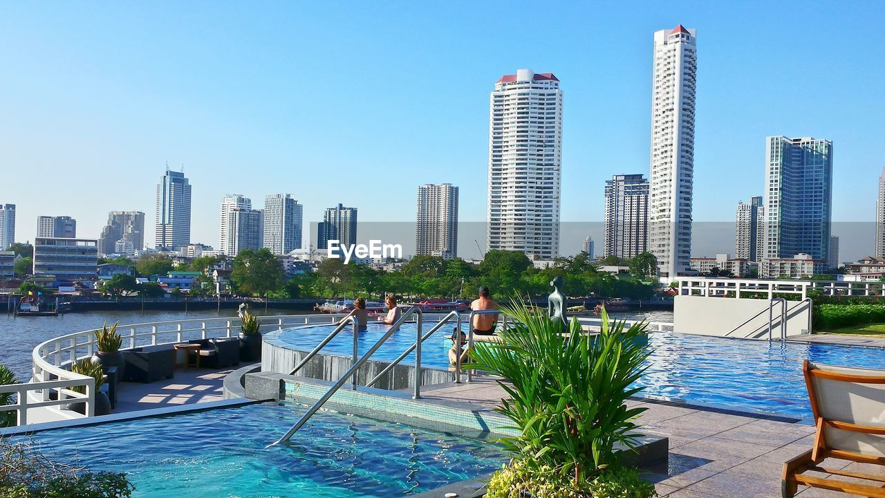 architecture, skyscraper, building exterior, built structure, water, modern, city, tower, day, clear sky, outdoors, luxury, sea, waterfront, swimming pool, luxury hotel, travel destinations, cityscape, urban skyline, no people, sky, nature