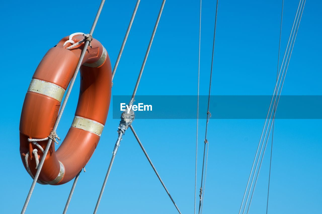 Low Angle View Of Life Belt Attached To Ropes Against Blue Sky