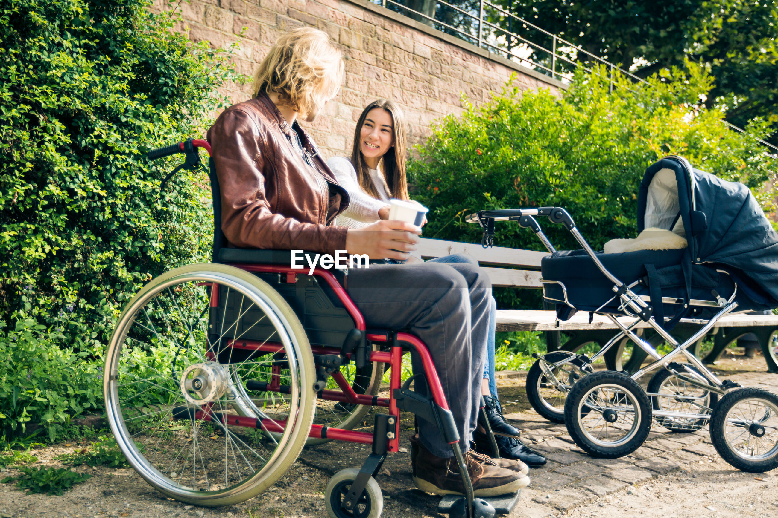 Man on wheelchair with woman sitting against wall