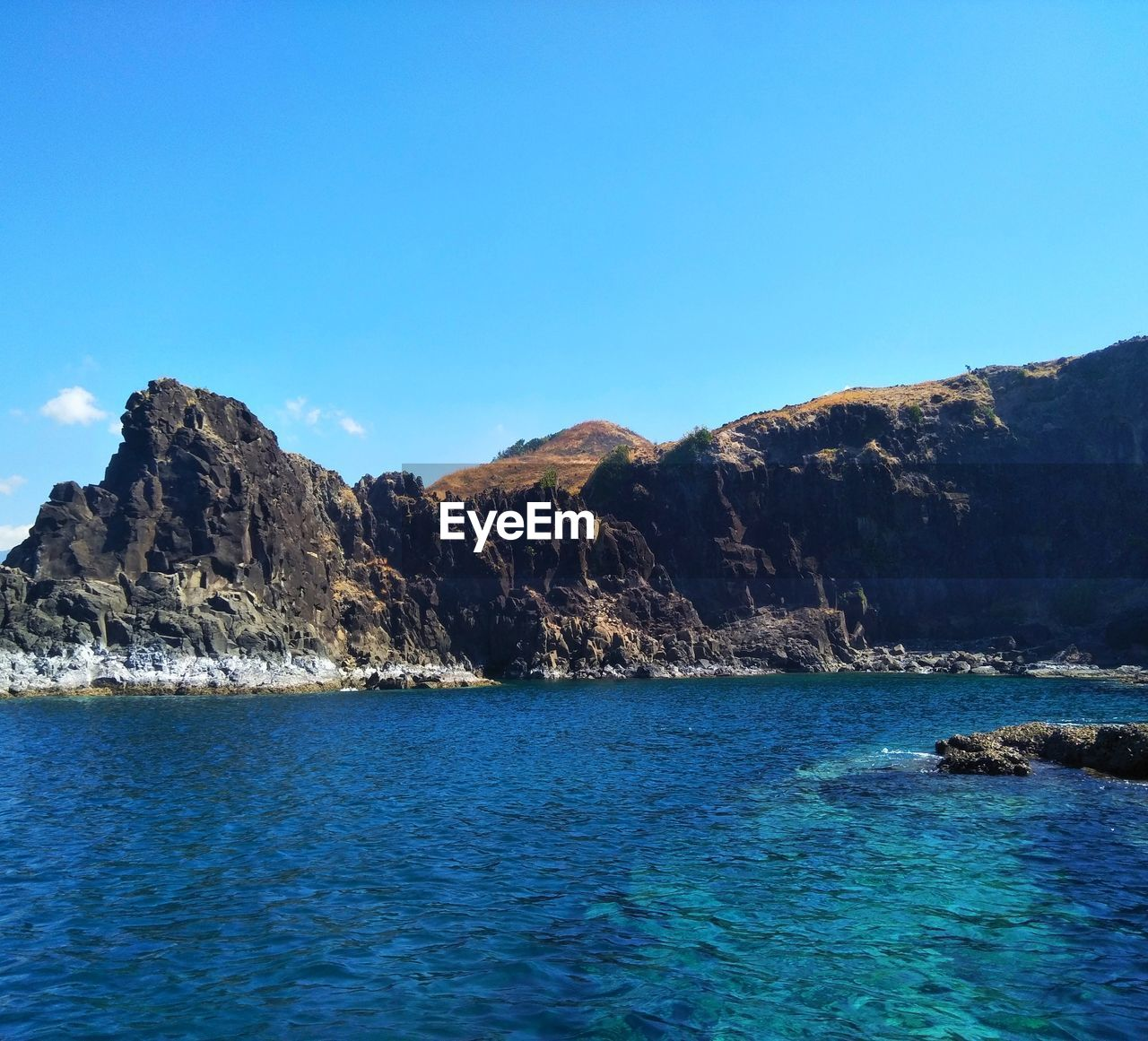 water, sky, sea, mountain, beauty in nature, blue, scenics - nature, nature, tranquility, waterfront, tranquil scene, rock, clear sky, copy space, no people, day, outdoors, idyllic, environment, formation, turquoise colored, view into land