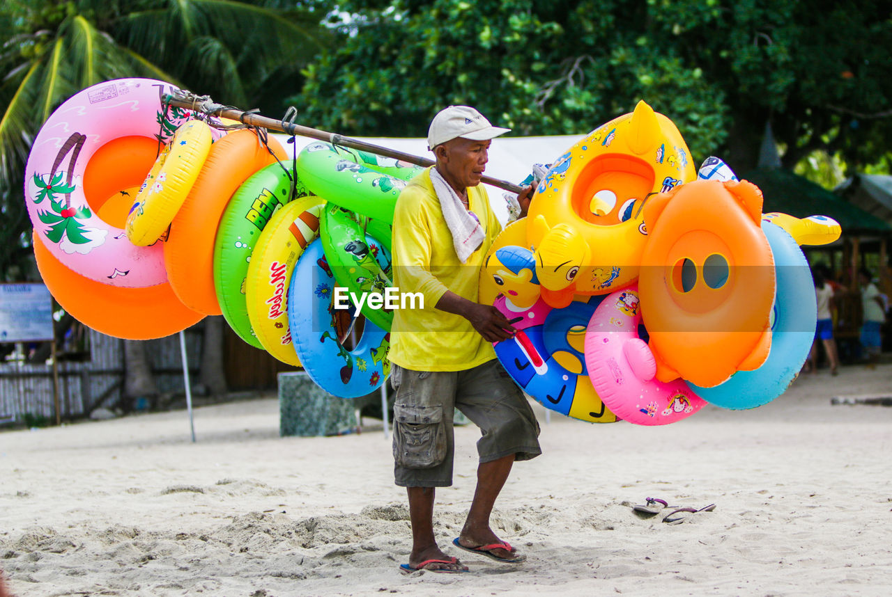 full length, one person, inflatable ring, real people, day, standing, leisure activity, outdoors, casual clothing, childhood, lifestyles, balloon, looking at camera, happiness, portrait, multi colored, boys, young adult, tree, men, one man only, sand pail and shovel, adult, people