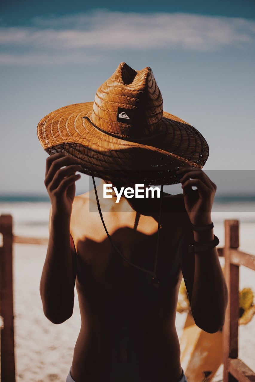 water, sea, hat, one person, focus on foreground, clothing, real people, sky, lifestyles, nature, beach, leisure activity, holding, waist up, land, day, women, standing, sun hat, outdoors, horizon over water, obscured face