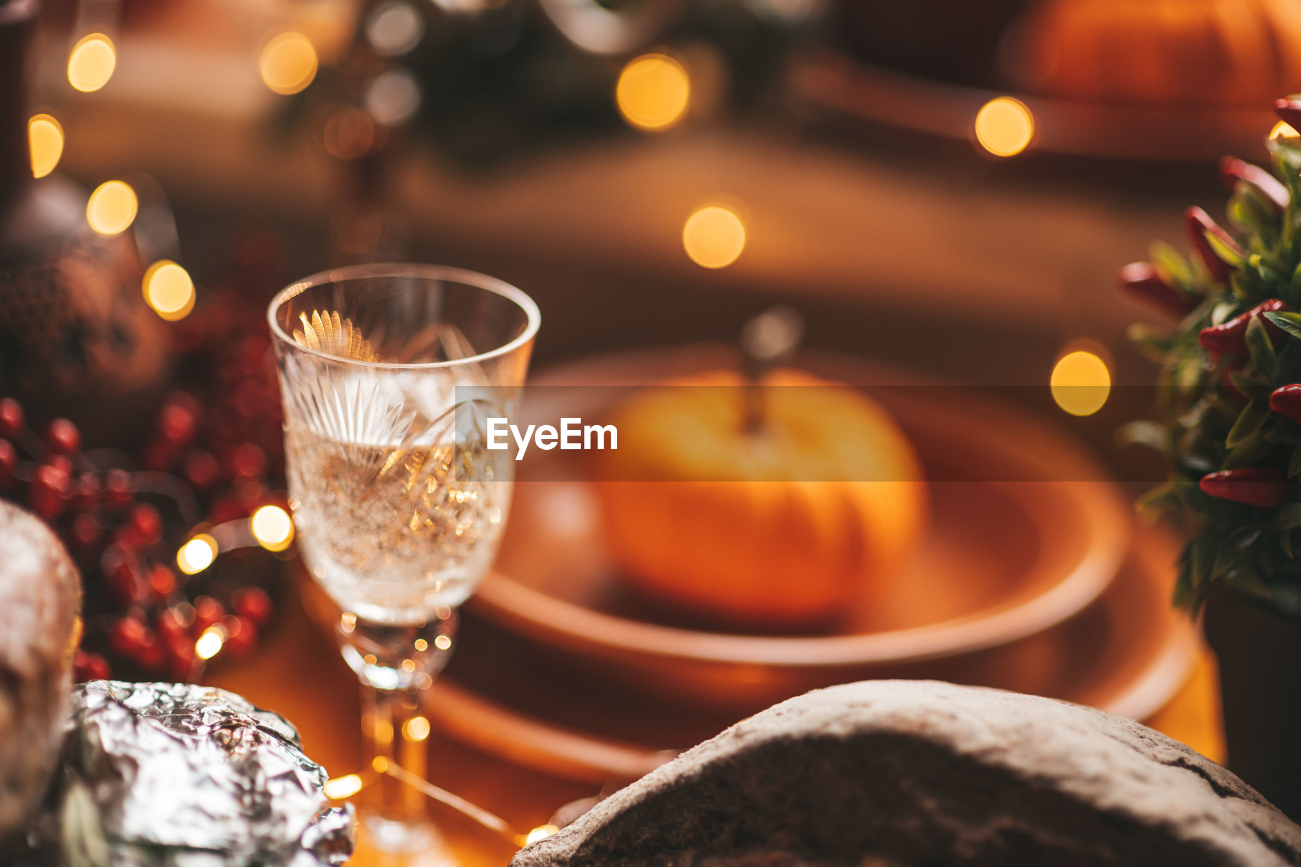 CLOSE-UP OF WINE GLASS ON TABLE AGAINST ILLUMINATED CHRISTMAS