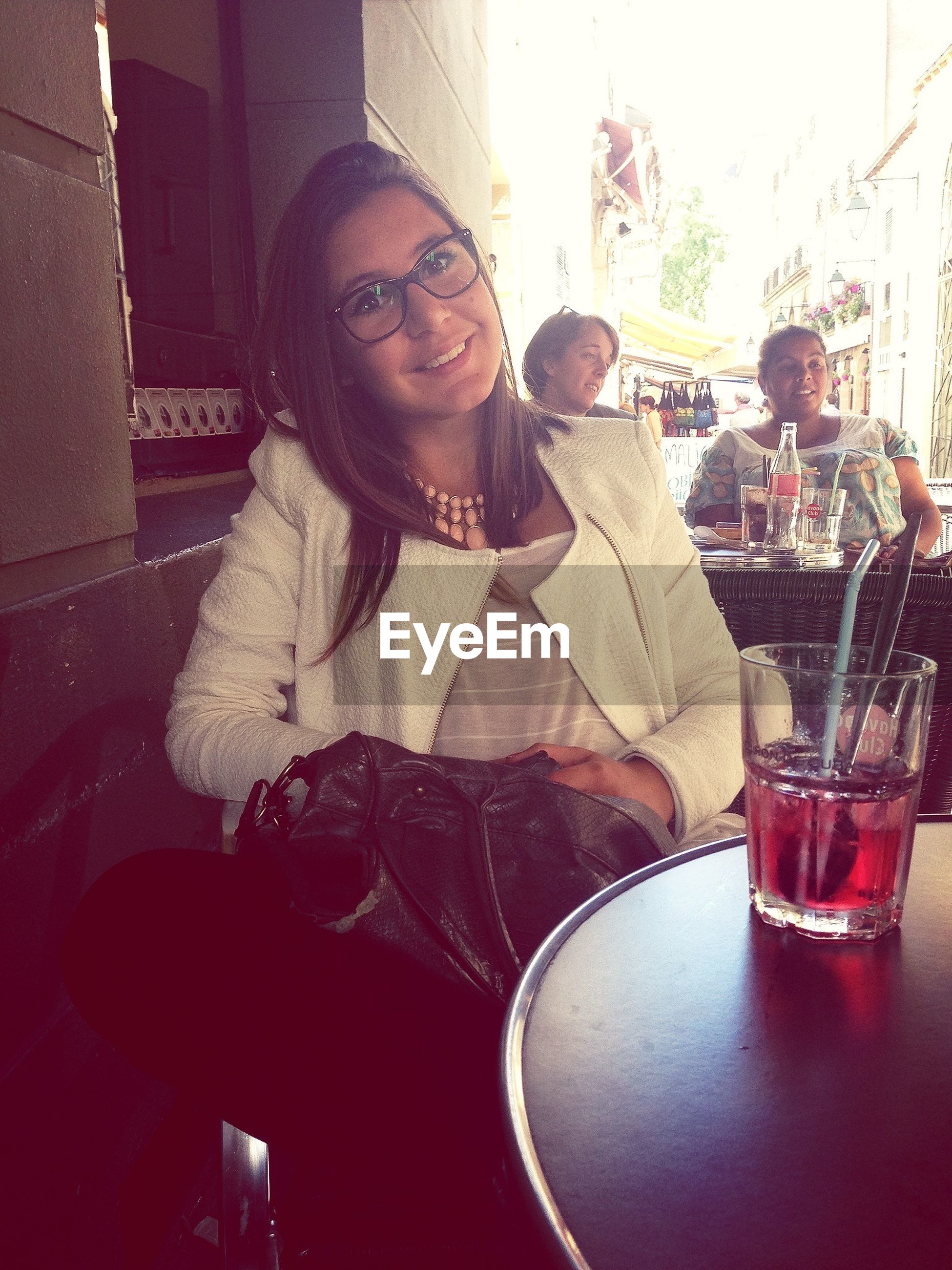 young adult, lifestyles, indoors, person, leisure activity, sitting, casual clothing, young women, looking at camera, portrait, sunglasses, front view, table, waist up, three quarter length, drink, food and drink