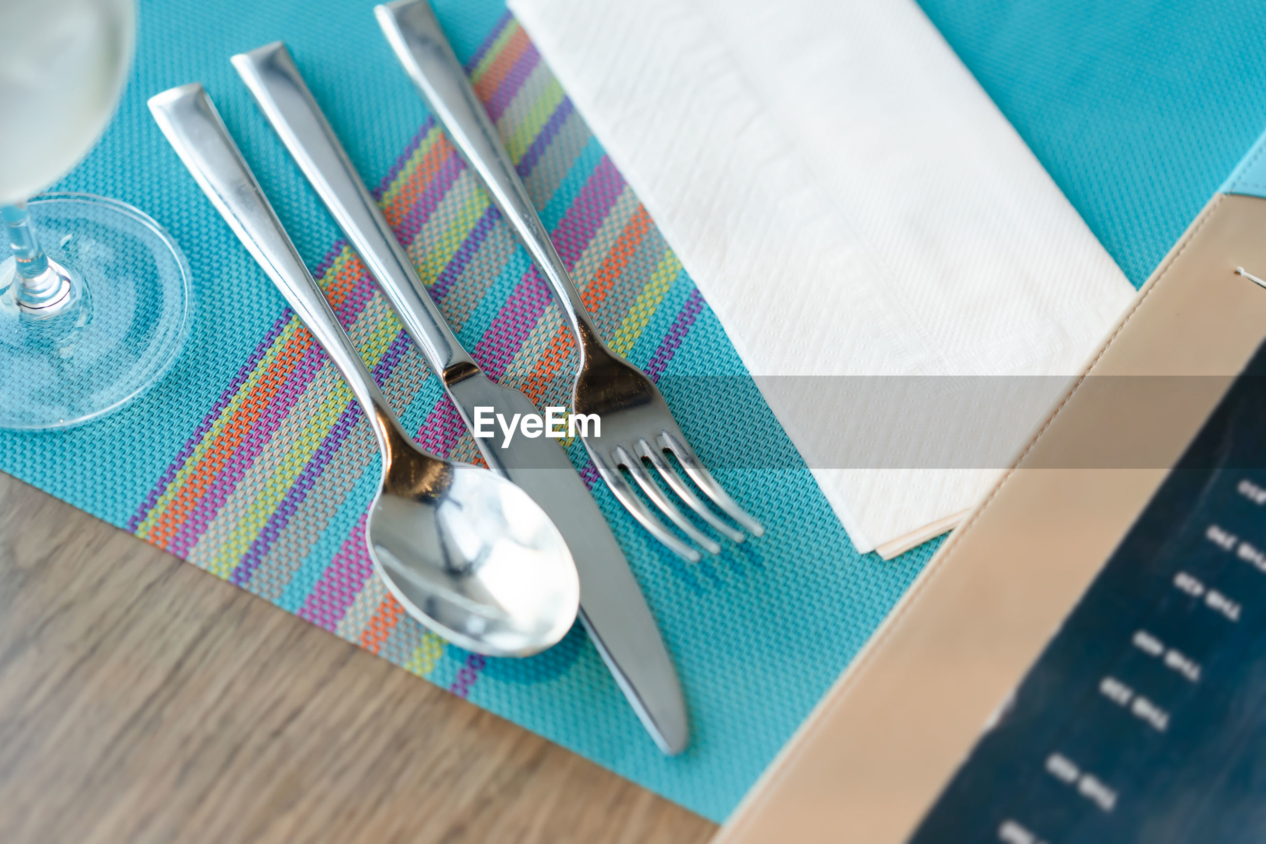Close-up of fork and spoon on place mat