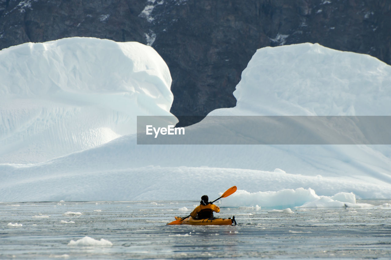 Rear View Of Person In Boat On Sea During Winter