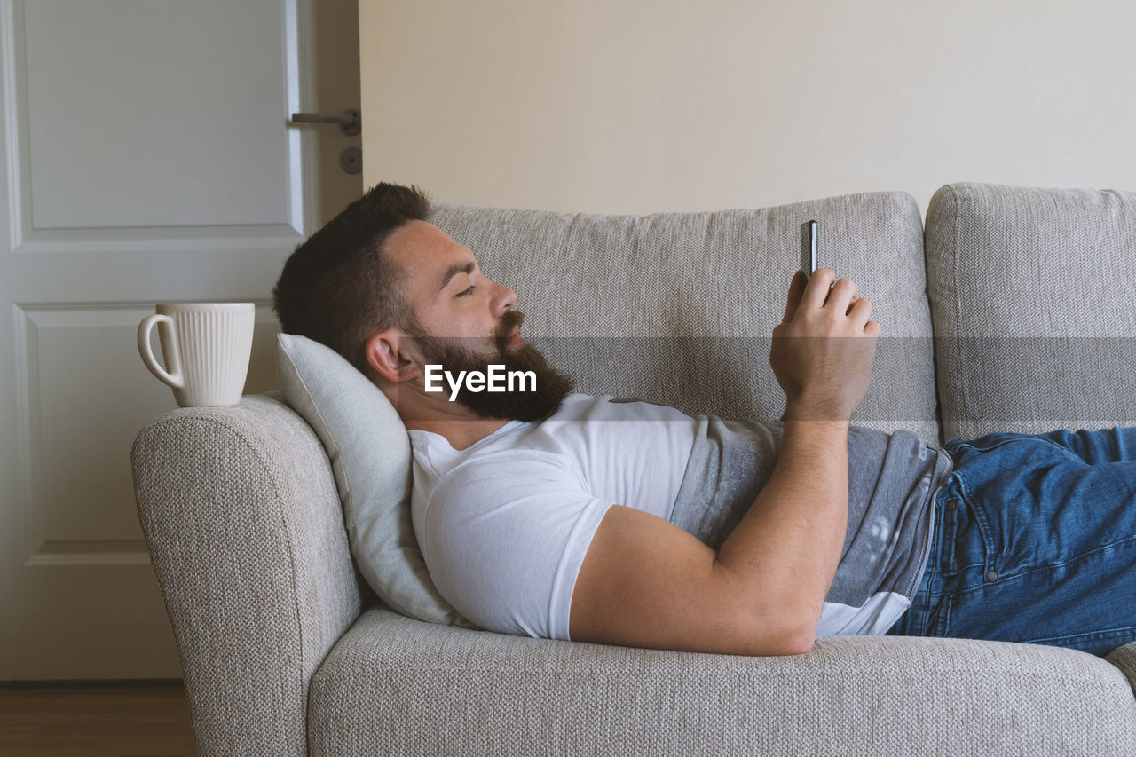 Profile view of man with beard using phone on sofa at home