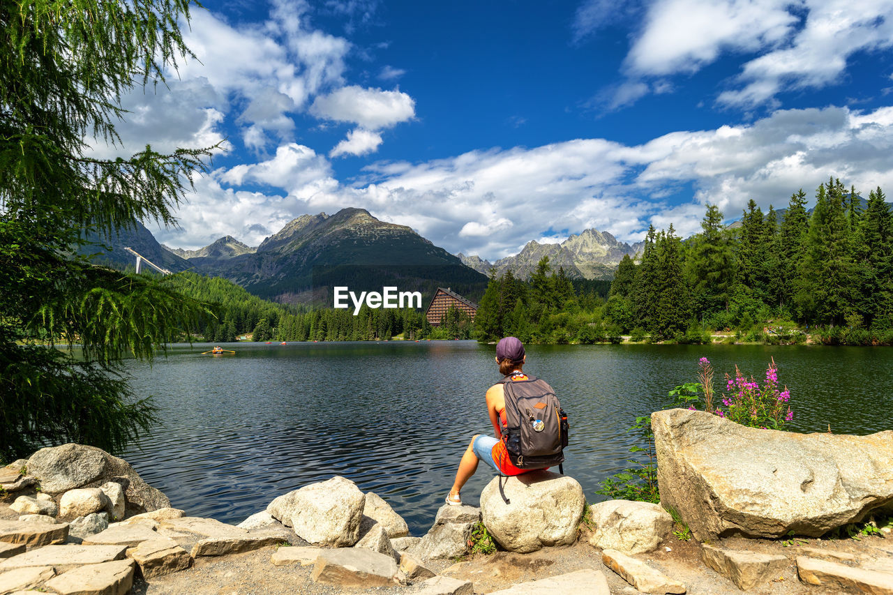 WOMAN SITTING ON ROCKS BY LAKE AGAINST MOUNTAINS