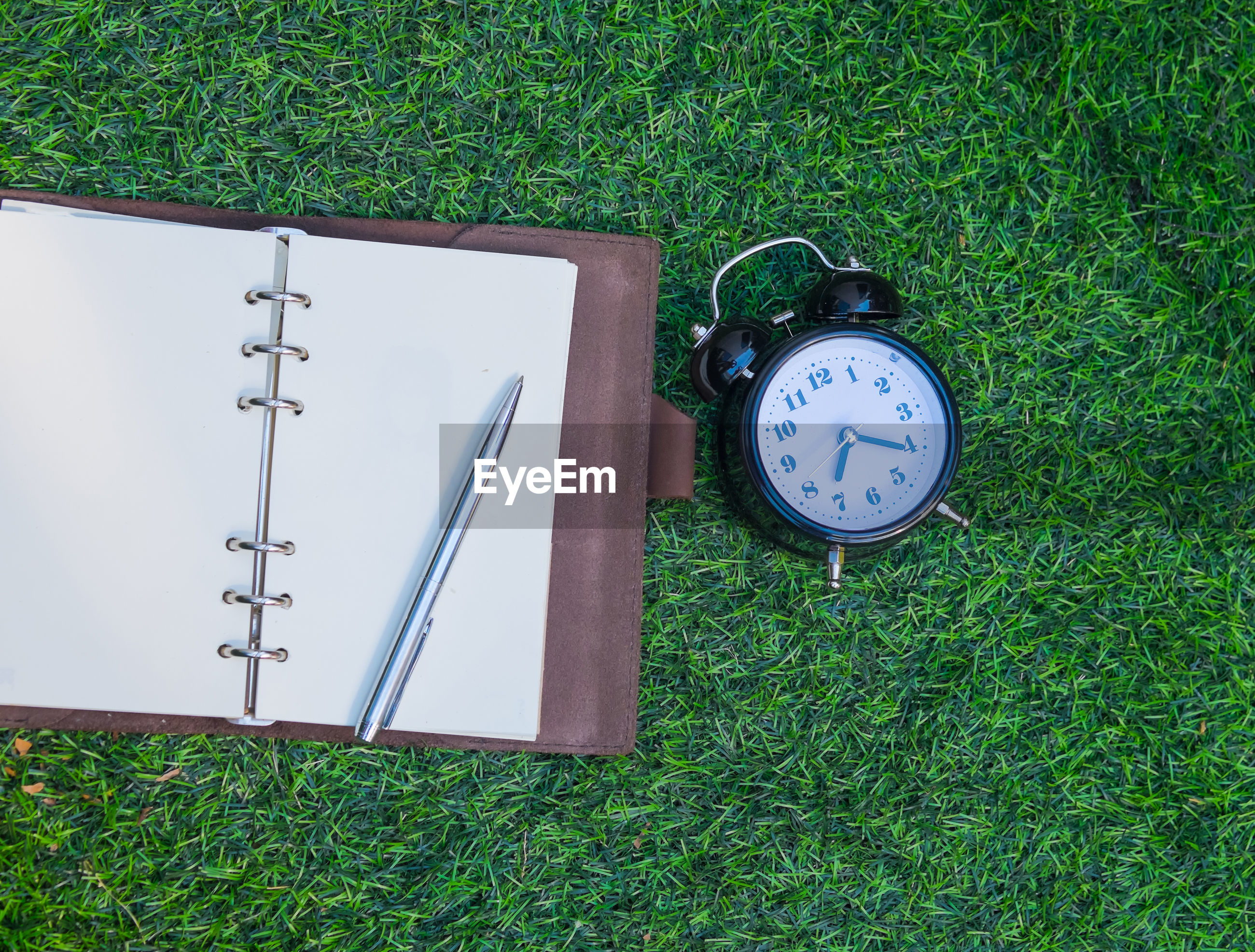 High angle view of clock and book on field