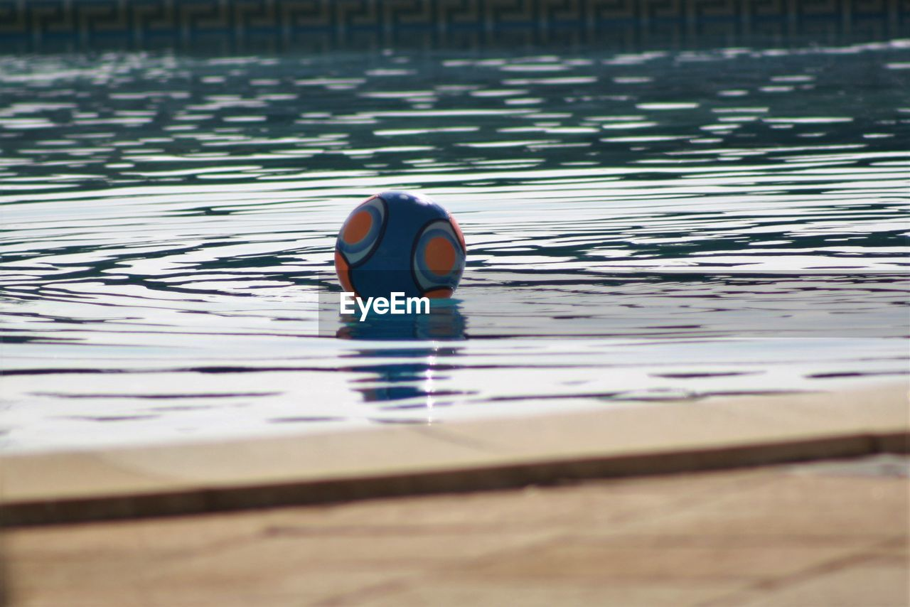 Surface level of ball in swimming pool