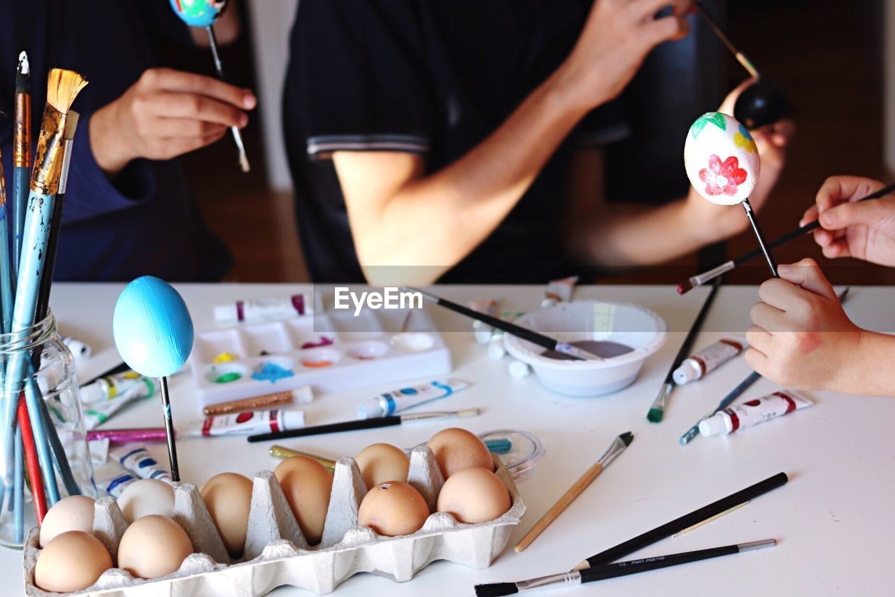 Close-Up Of People Decorating Easter Eggs