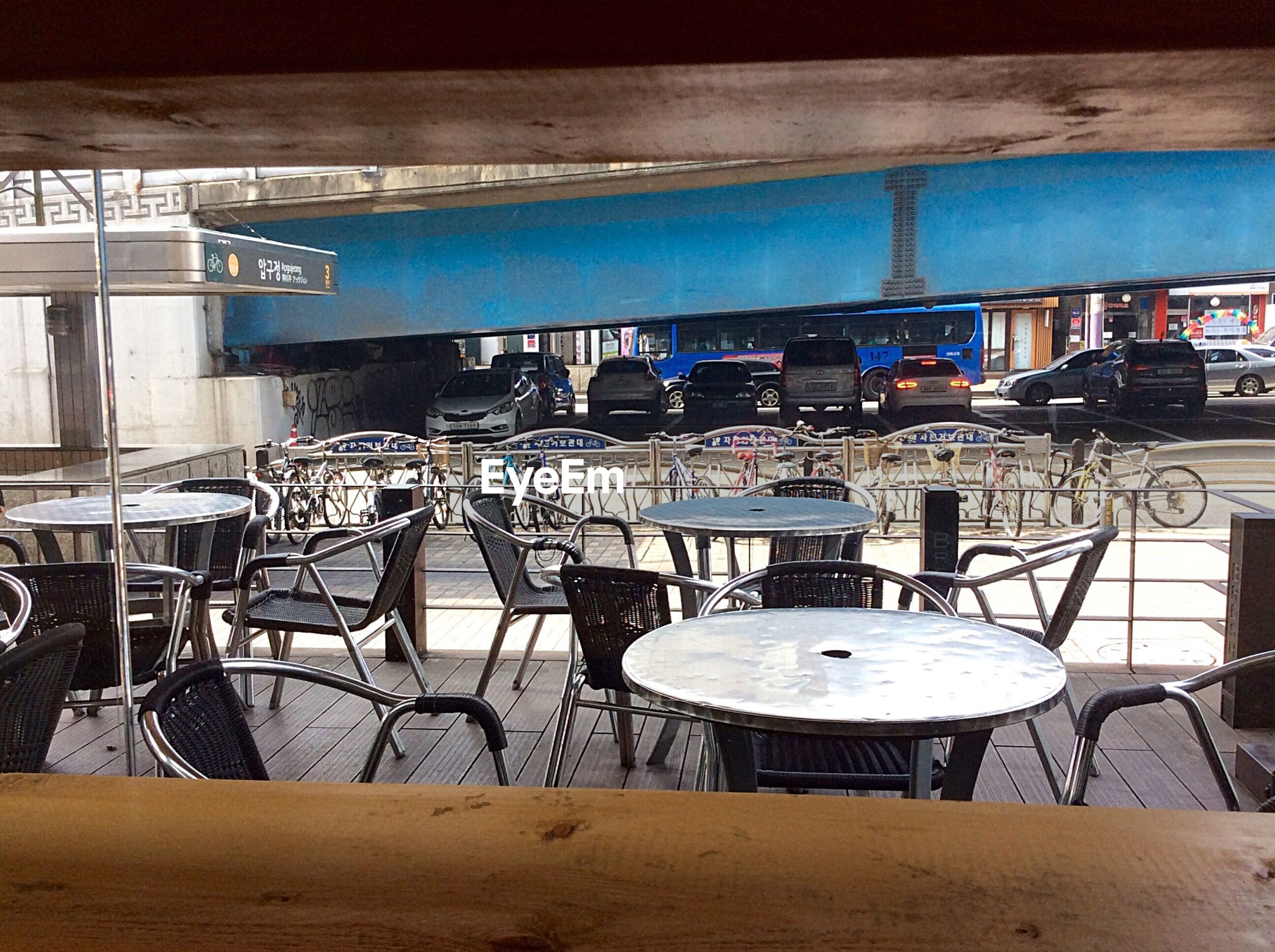 chair, absence, table, empty, built structure, restaurant, architecture, indoors, arrangement, seat, sunlight, group of objects, no people, day, large group of objects, building exterior, sidewalk cafe, blue, cafe, in a row