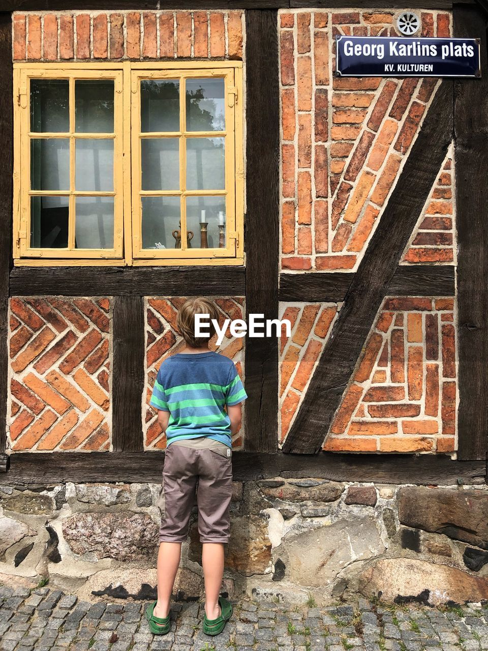 FULL LENGTH REAR VIEW OF BOY STANDING AGAINST WINDOW