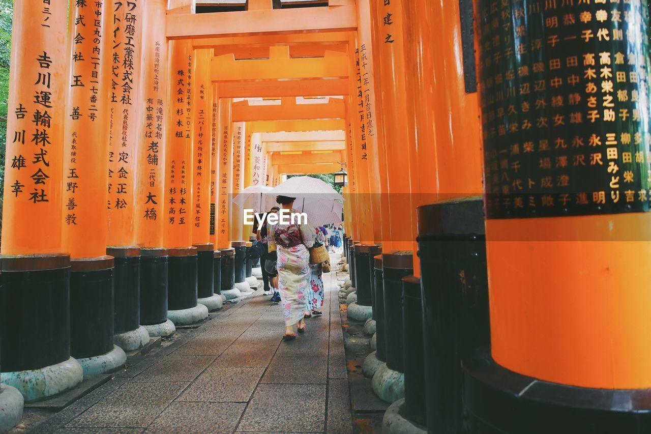 Rear View Of Women Walking On Walkway Amidst Torii Gates
