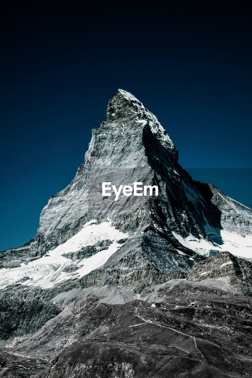 Low angle view of matterhorn mountain against clear blue sky