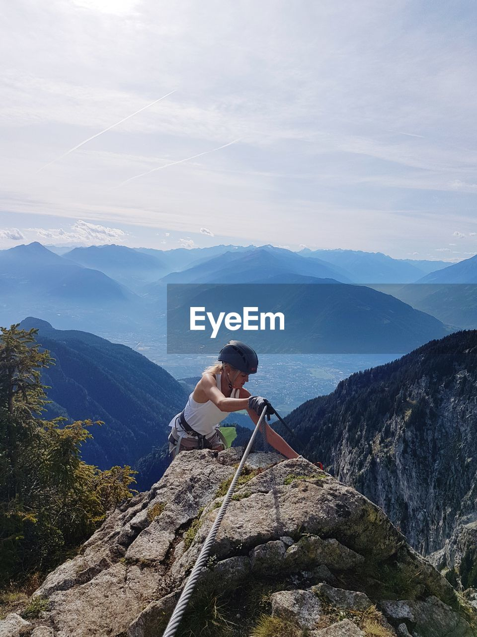 Woman climbing on rock by mountains against sky