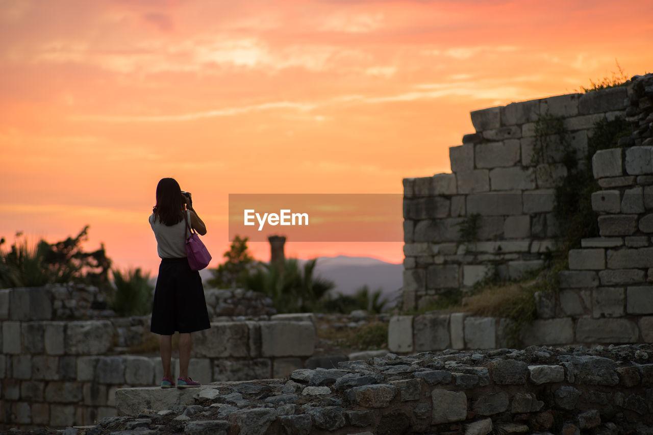 Rear view of woman standing on ruins in castle against orange sky