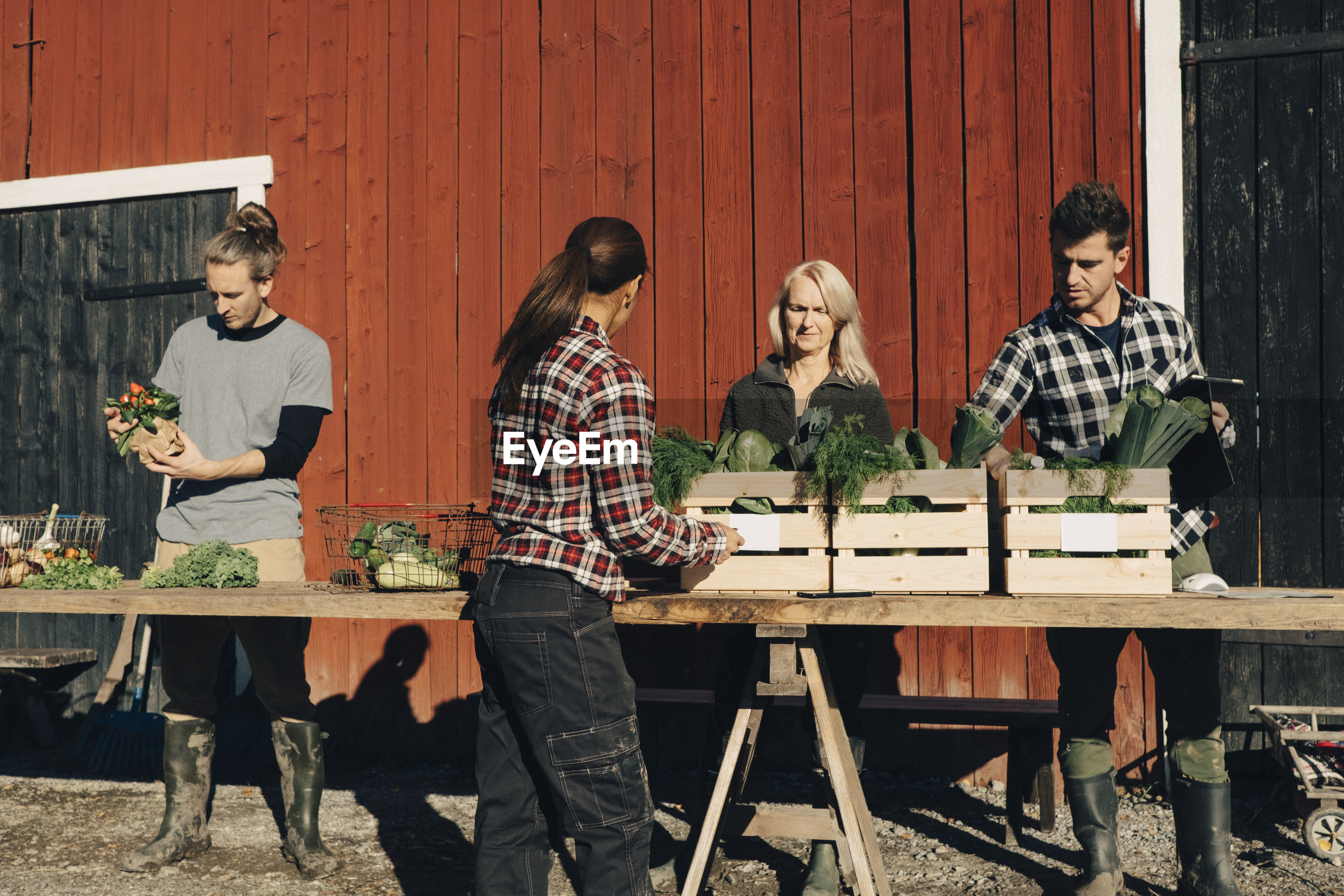 GROUP OF PEOPLE SITTING ON WOODEN TABLE AGAINST WALL