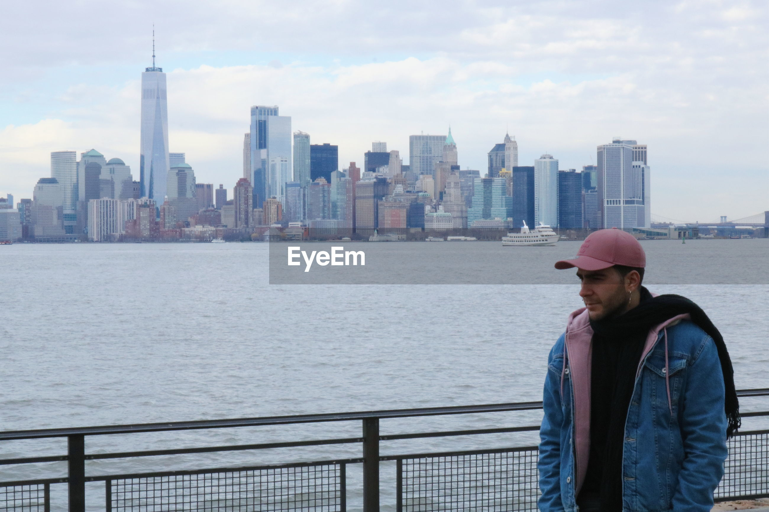 Young man standing by river in city at manhattan