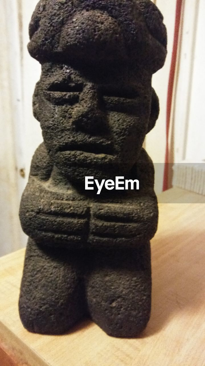 representation, close-up, indoors, no people, art and craft, focus on foreground, still life, sculpture, human representation, table, statue, male likeness, craft, creativity, wood - material, carving - craft product, religion, toy, spirituality, home interior