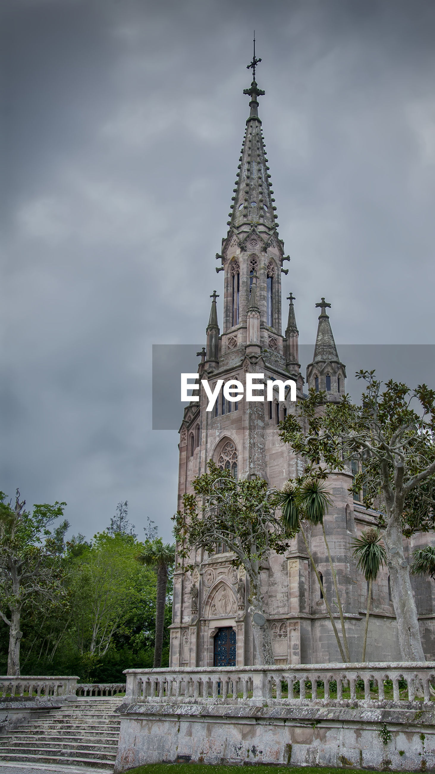 religion, place of worship, spirituality, cloud - sky, architecture, sky, low angle view, day, built structure, building exterior, travel destinations, outdoors, history, tree, no people, clock tower, bell tower