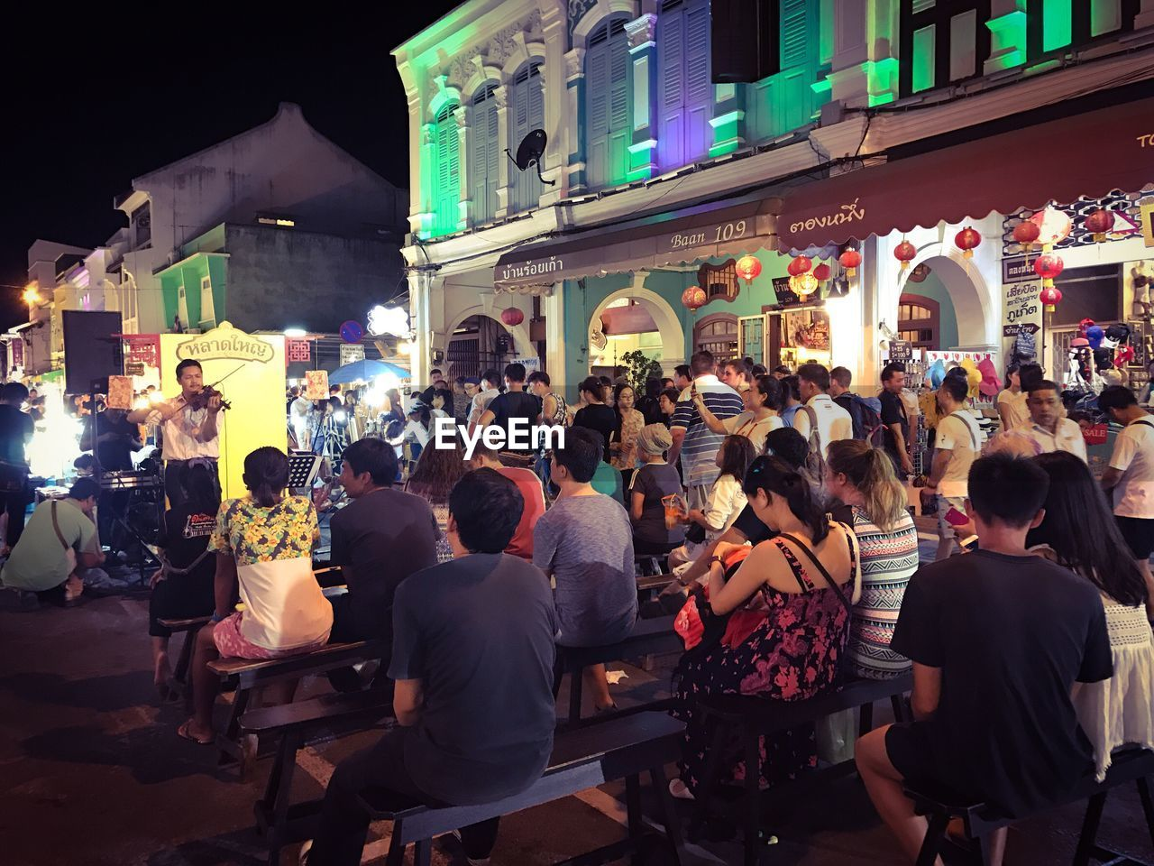large group of people, architecture, building exterior, built structure, real people, women, night, men, crowd, leisure activity, city life, illuminated, lifestyles, city, outdoors, sky, people, adult